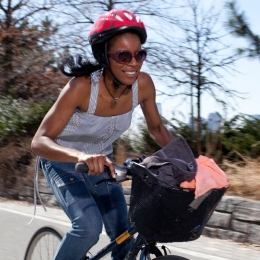 A woman rides a bike with a full basket and a smile