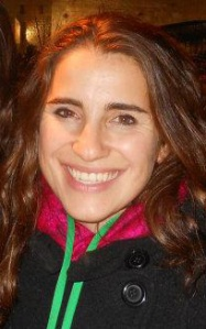 A woman in a coat smiles at the camera